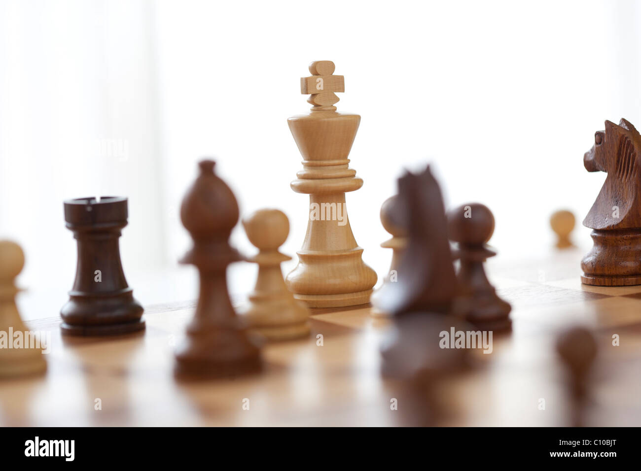 game of chess from eye level with king surrounded - Stock Image