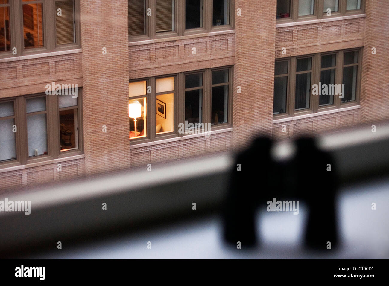 A pair of binoculars sit on a New York City apartment window sill looking out onto another apartment. - Stock Image