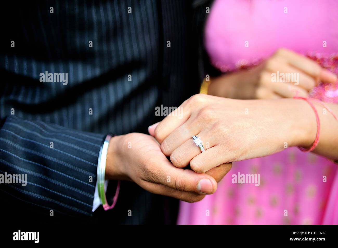 A close up shot of two people holding hands showing and engagement ring they are of Indian origin and Hindu - Stock Image