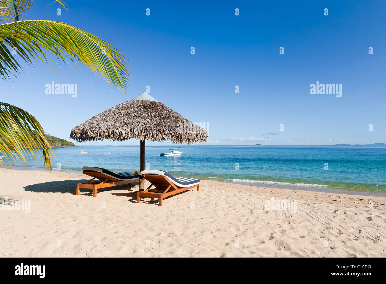 Tropical beach landscape with deckchair and parasol, from Nosy Be, Madagascar - Stock Image