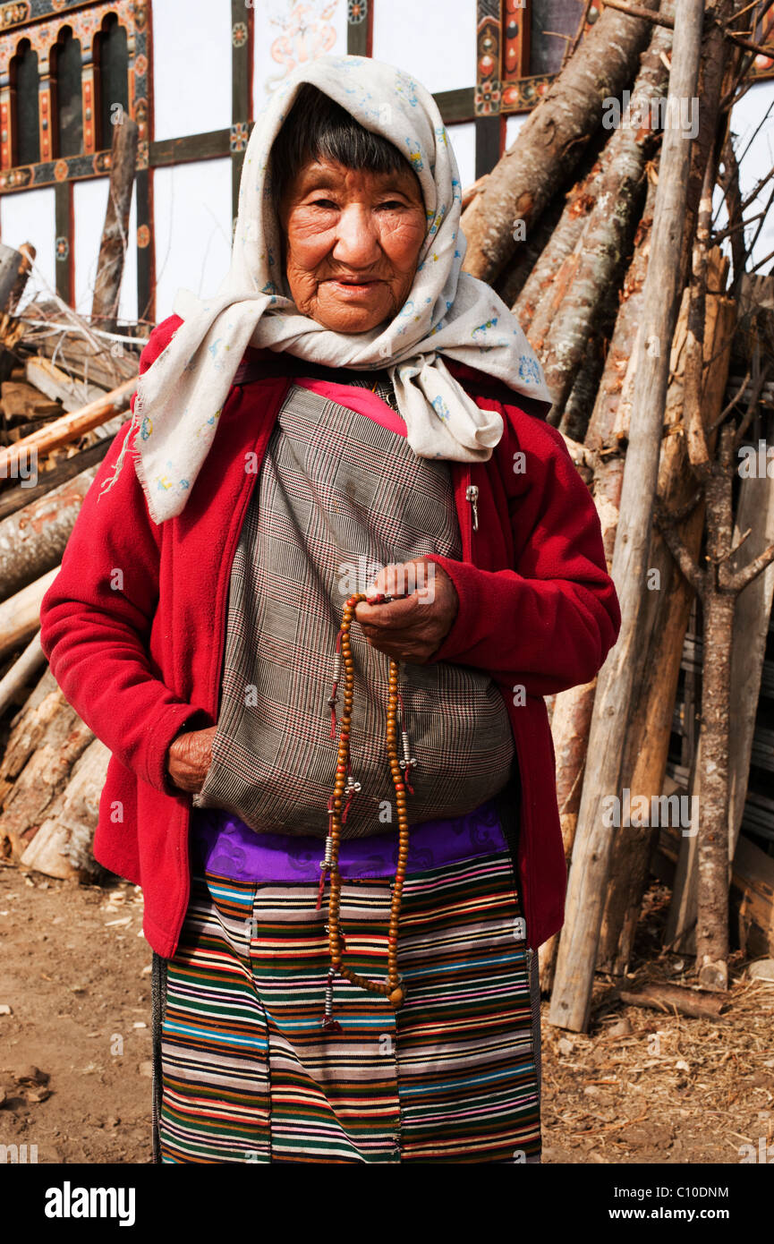 Older Bhutanese woman with prayer beads in traditional dress near Bhumtang, Bhutan - Stock Image
