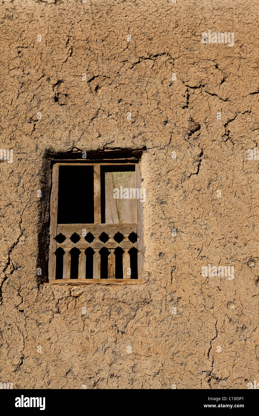 A wooden framed window in one of the red, earth coloured houses of the Omani village of Al Hamra. - Stock Image