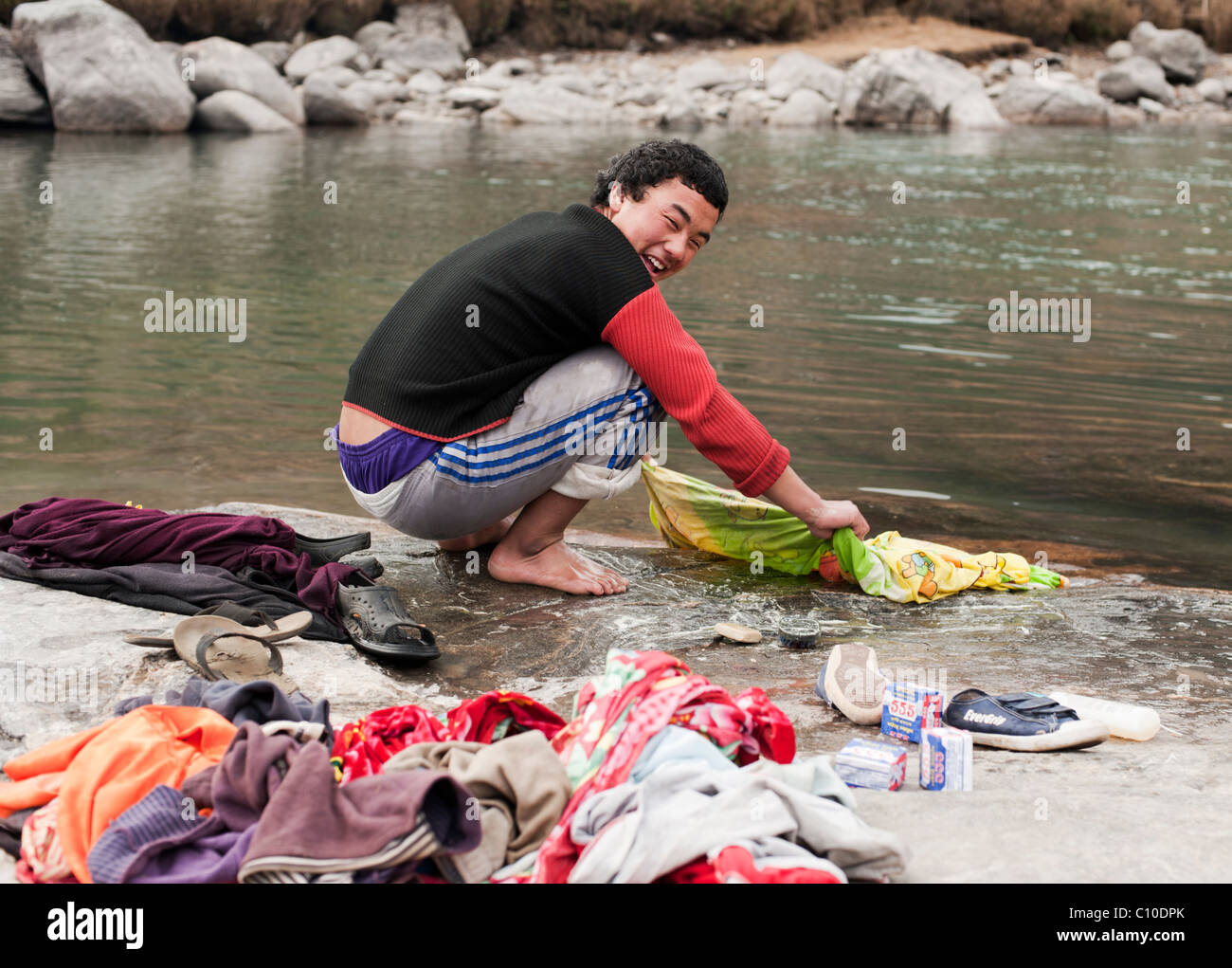 Young Bhutanese boy doing laundry in a river in Bumthang, Bhutan. - Stock Image