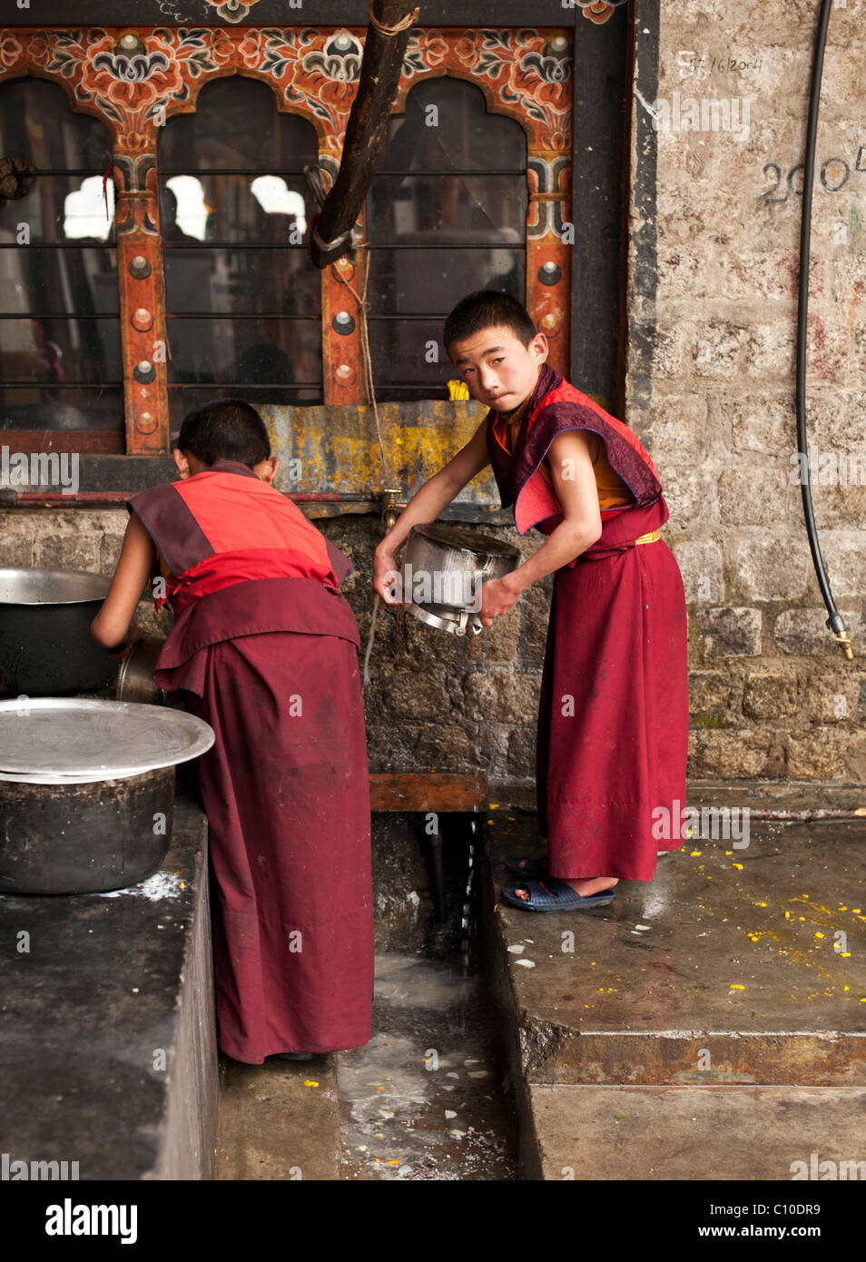 Two young Bhutanese Buddhist monks clean the dishes of the monastery after a meal at a temple in Central Bhutan - Stock Image