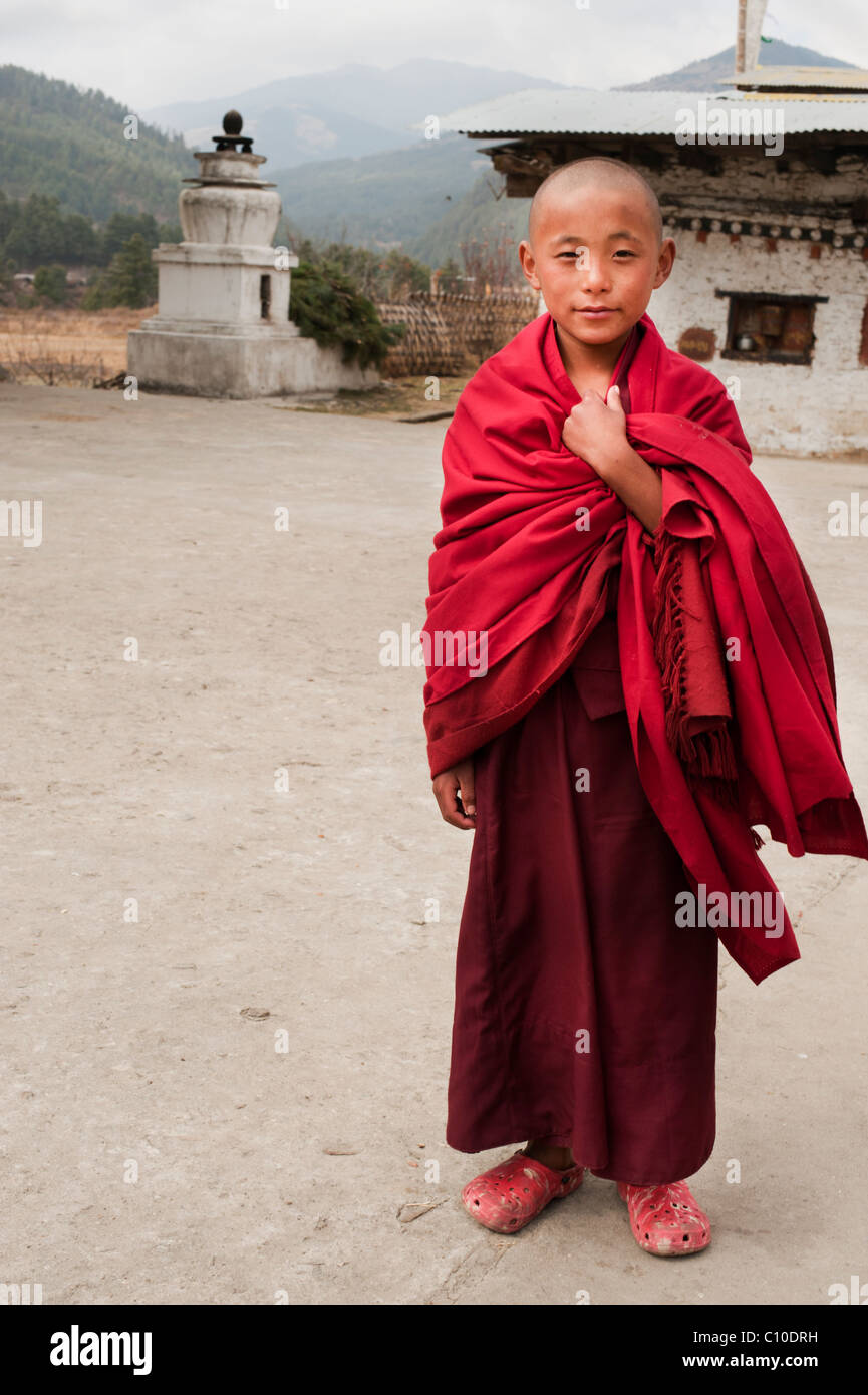 Young Bhutanese Buddhist monk walks across the temple grounds in a maroon robe on his way to perform his duties. - Stock Image