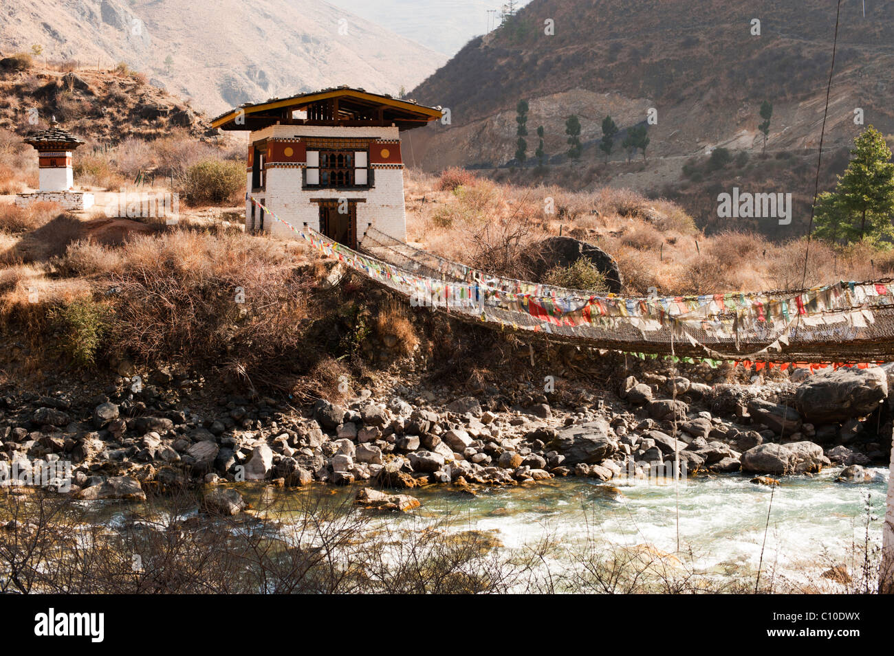 Bhutanese pedestrian suspension bridge over a river at the Temple of the Iron Master near Paro, Bhutan - Stock Image