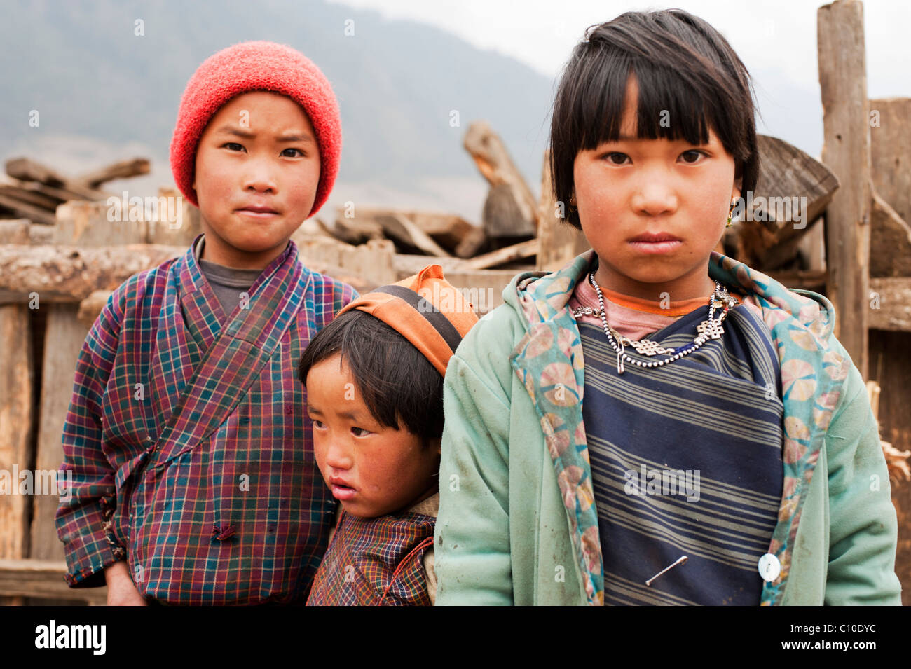 Two sisters and a brother standing in front of their farm on a cold winter's day in the mountains of central - Stock Image