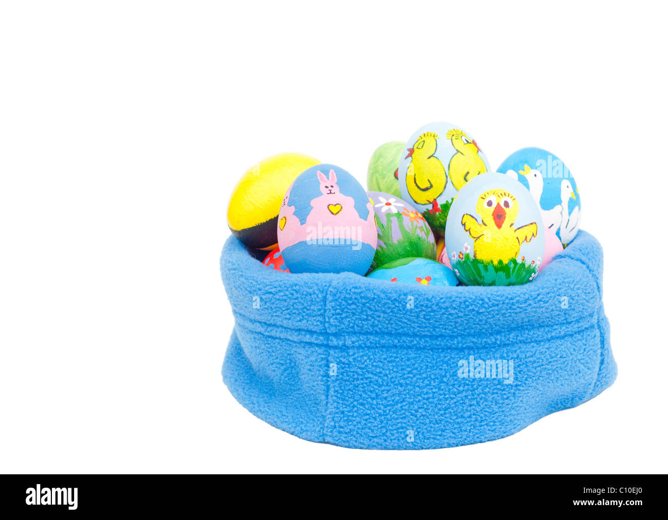 Delightfully colorful hand painted Easter eggs nested in blue fleece on white background - Stock Image