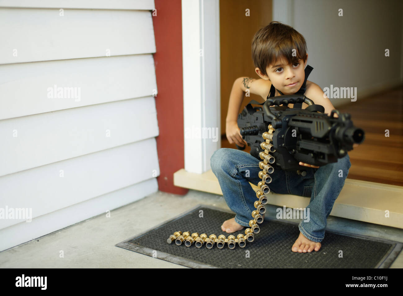 Seven year old boy sits on doorstep holding toy machine gun - Stock Image