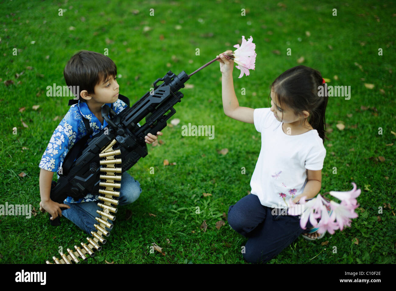 Five year old girl places flowers in barrel of her brother's toy machine gun - Stock Image