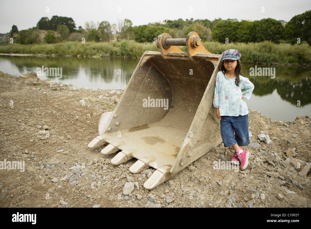Five year old girl leans against digger shovel at the construction of flood defences, Manawatu river, Palmerston - Stock Image