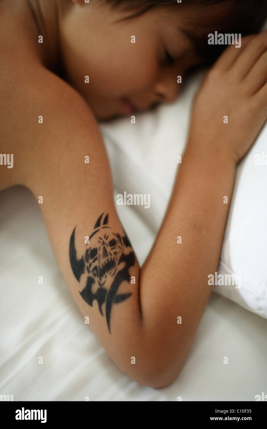 Seven year old boy with temporary skull tattoo sleeping in bed - Stock Image