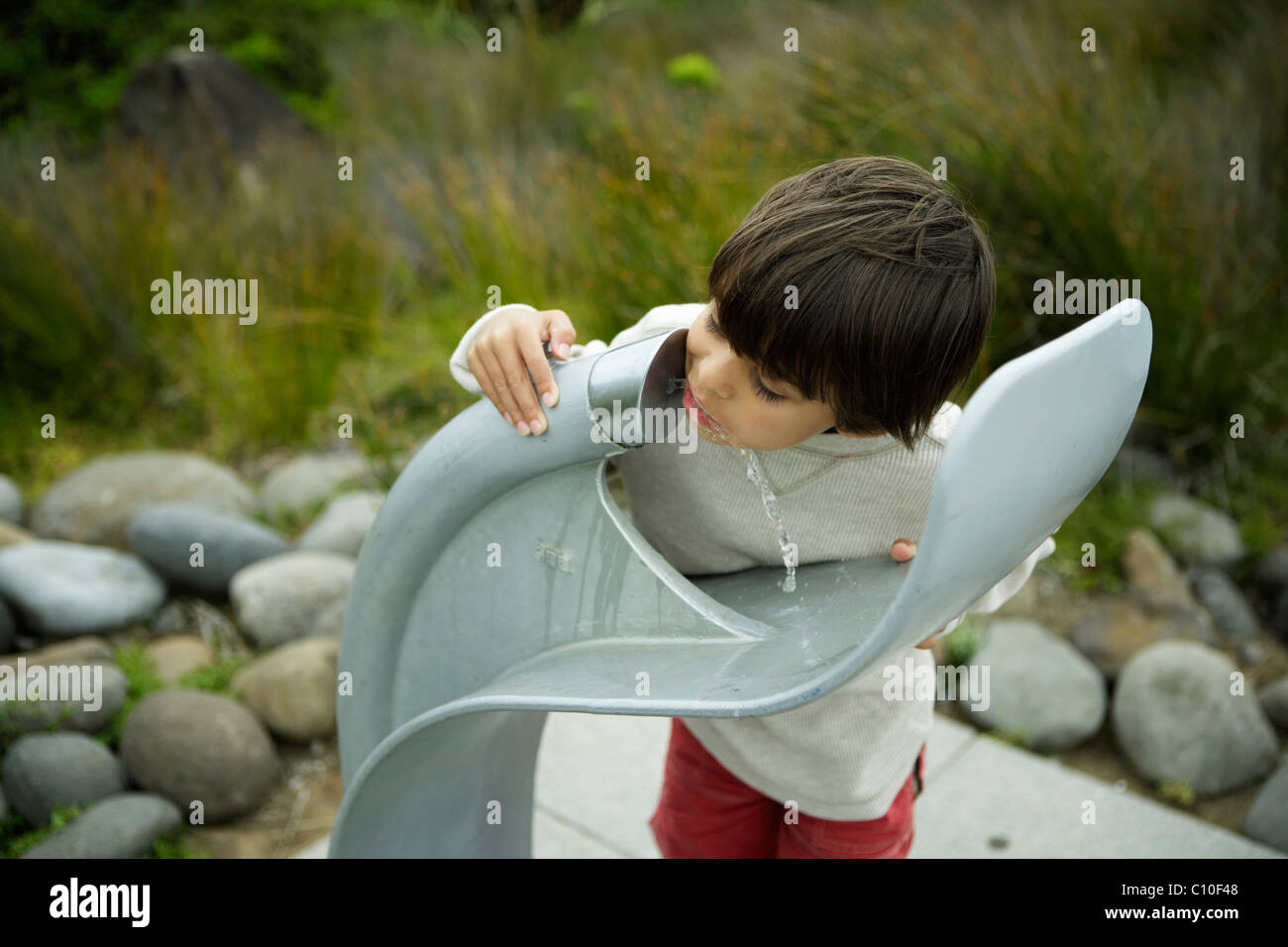 Boy drinks from water fountain - Stock Image