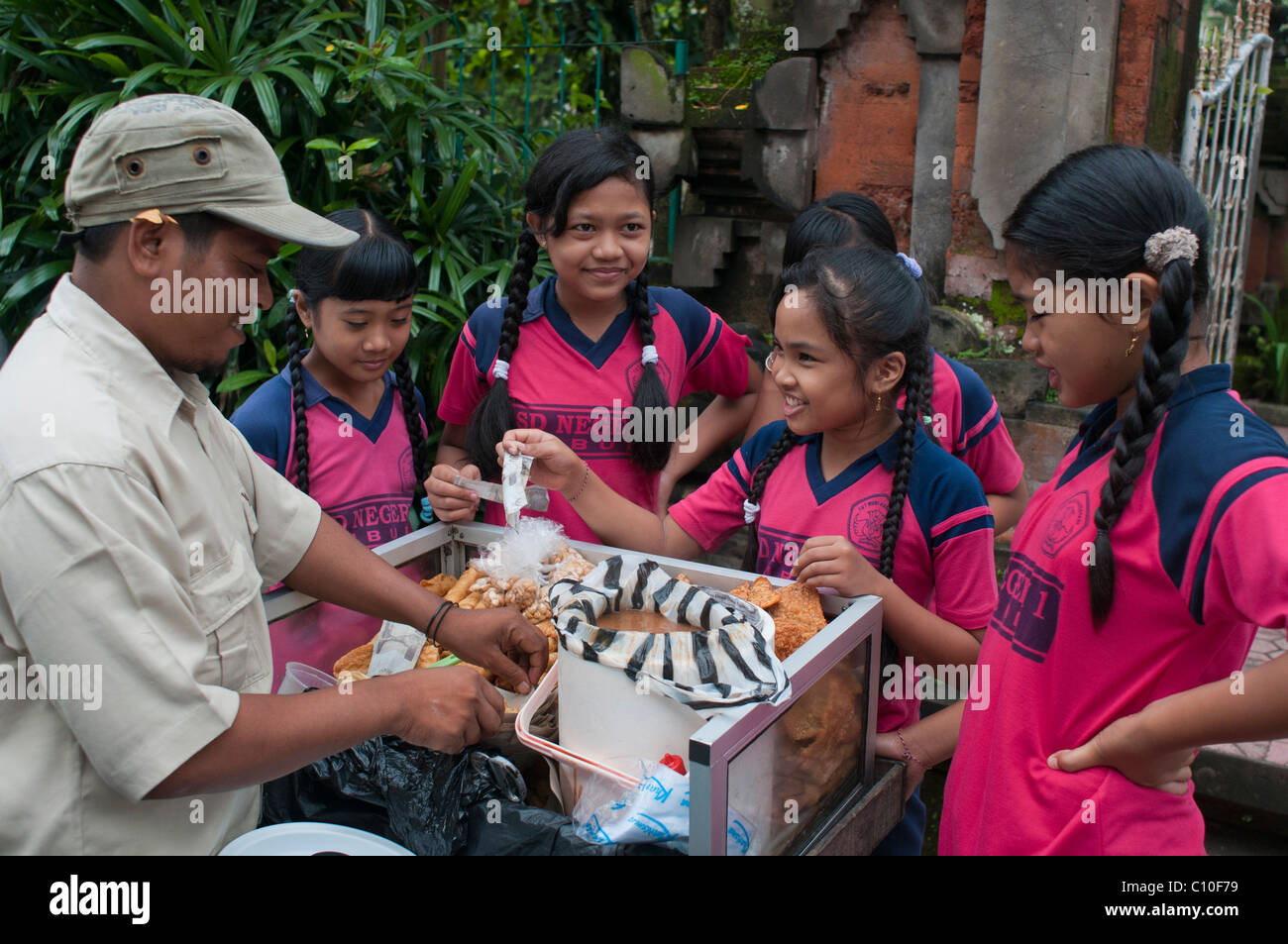 Indonesian primary school children buying after school treats from a street vendor outside their school in Ubud - Stock Image