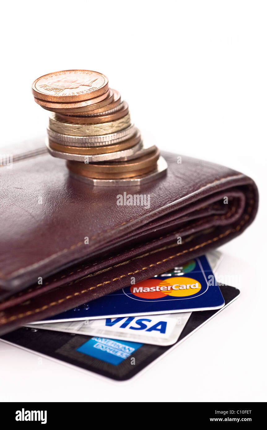 Empty pursue with a pile of coins and credit cards - Stock Image