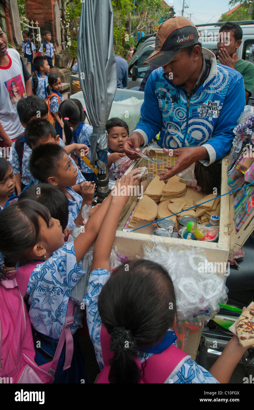 Indonesian primary school children buying after school treats from a street vendor outside their school in Ubud, - Stock Image