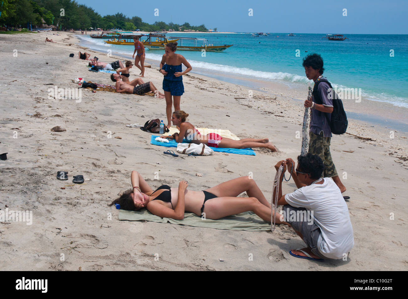 Trinket sellers pestering sunbather on beach on Gili Trawangan a small island off the costs of Lombok - Stock Image
