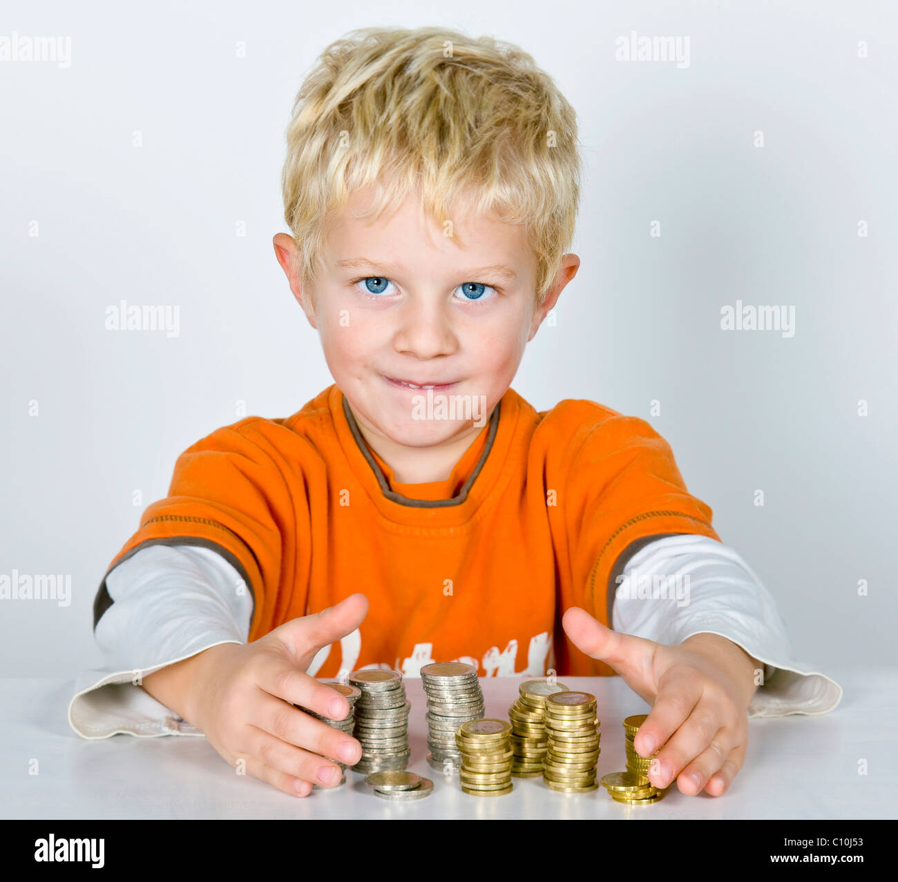 Boy, 5-years old, stacks of money, symbolic picture for making profit - Stock Image