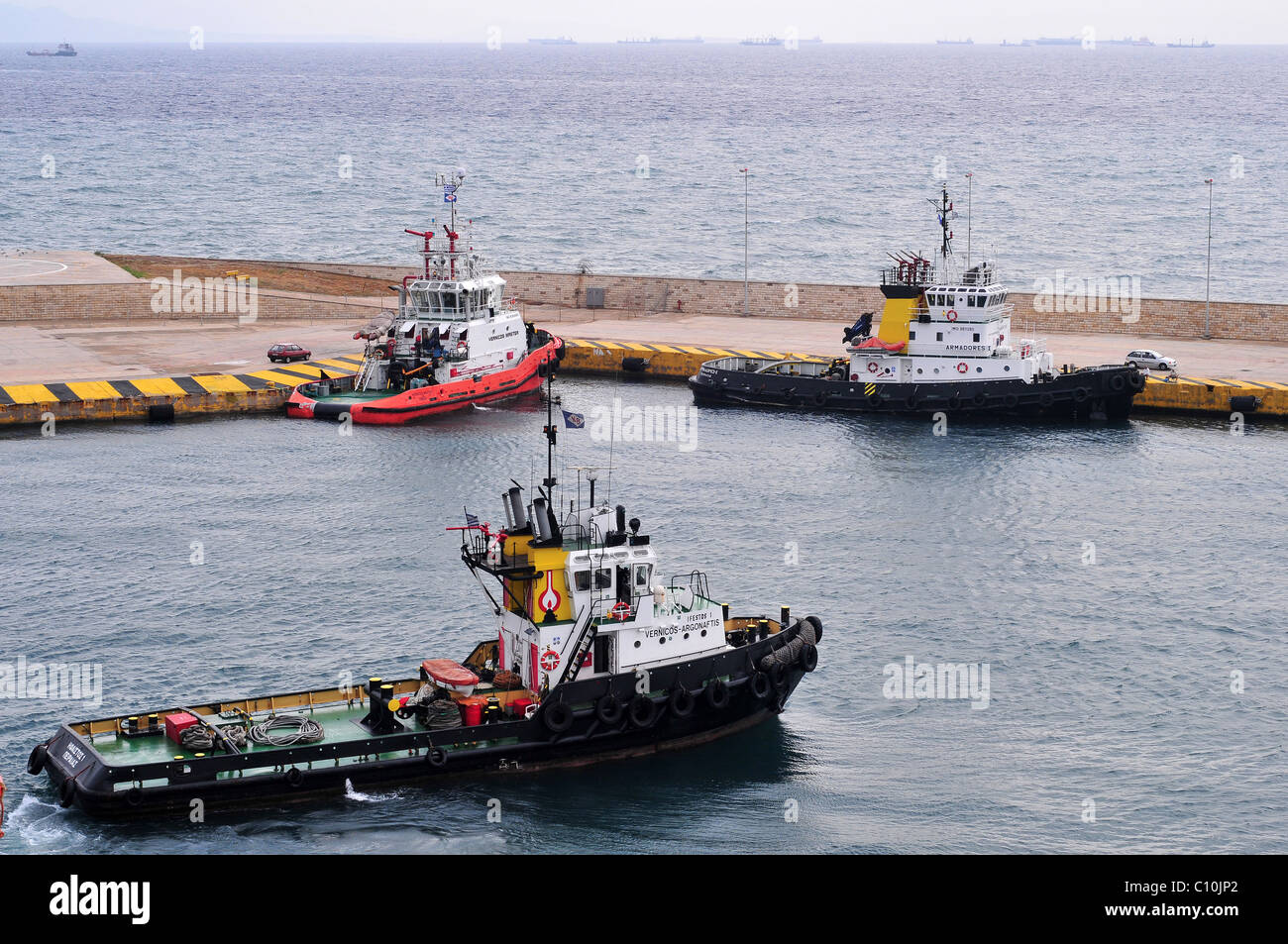 Three tugs waiting near the harbour breakwater at Pireas, Athens, Greece - with ships waiting to dock shown in the - Stock Image