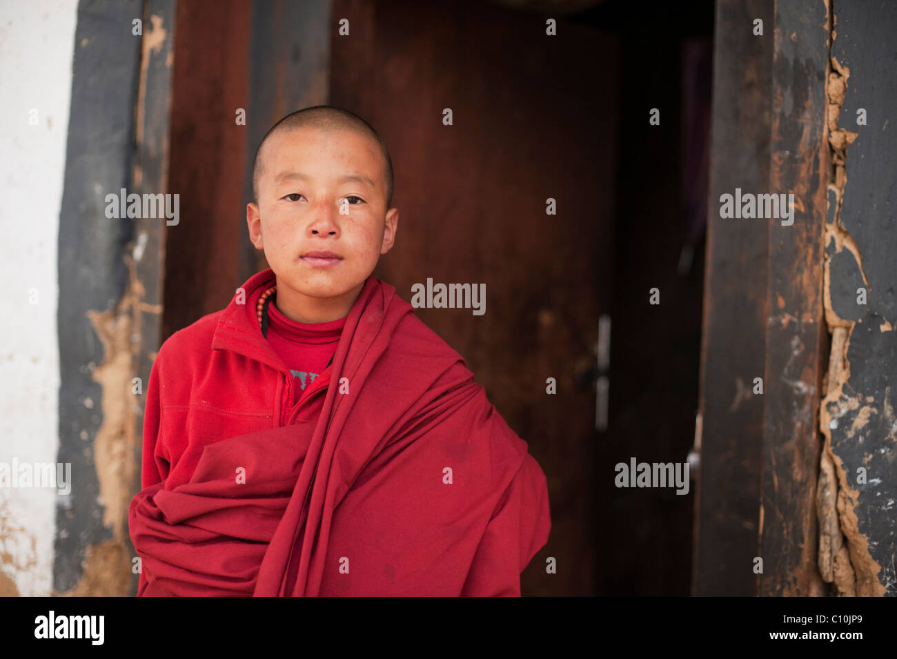 Young and proud Bhutanese monk standing in a doorway of a temple in rural Bhutan - Stock Image