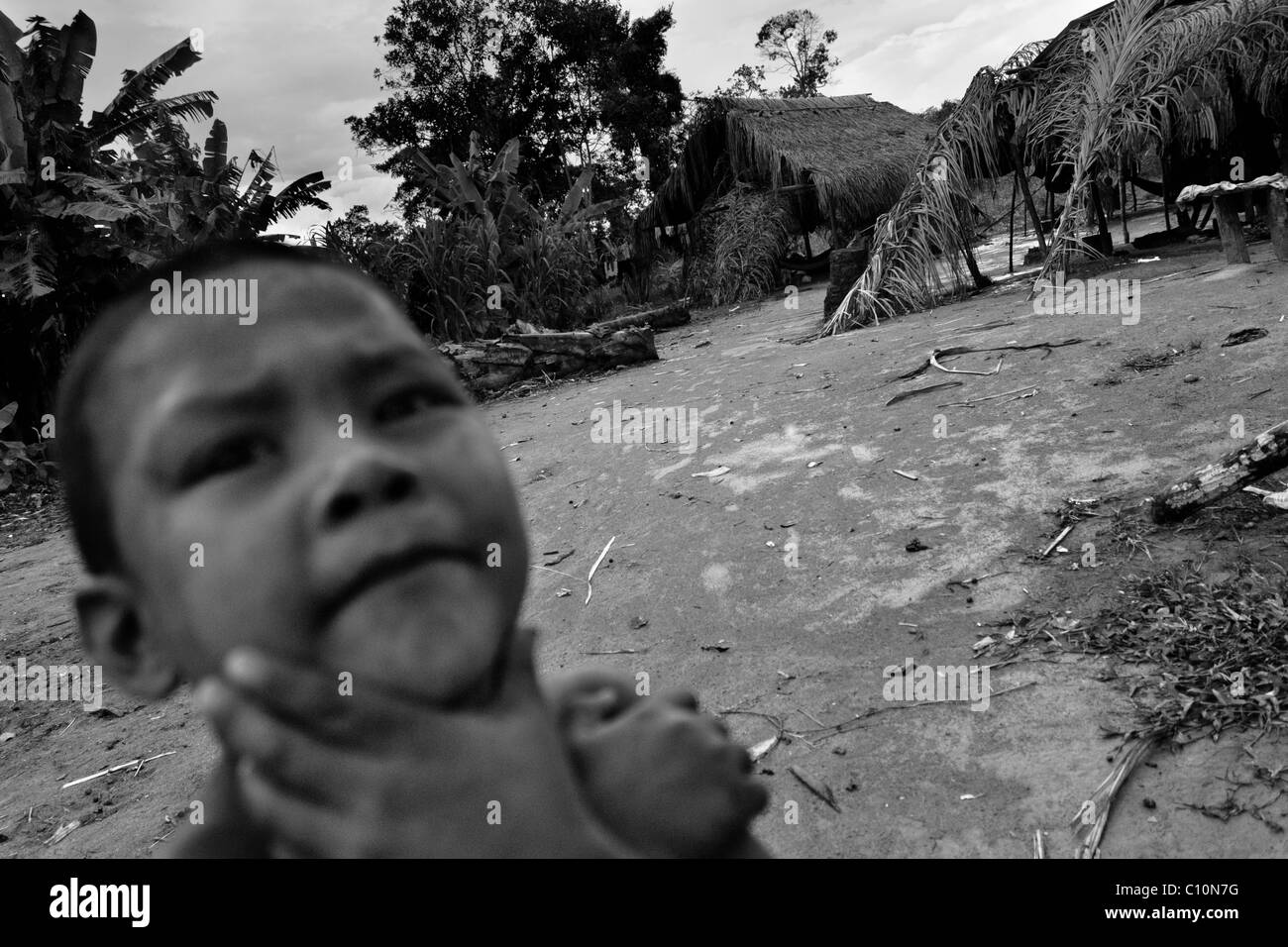 A young Nukak boy stands in front of the shacks in a refugee settlement close to San Jose del Guaviare, Colombia. - Stock Image