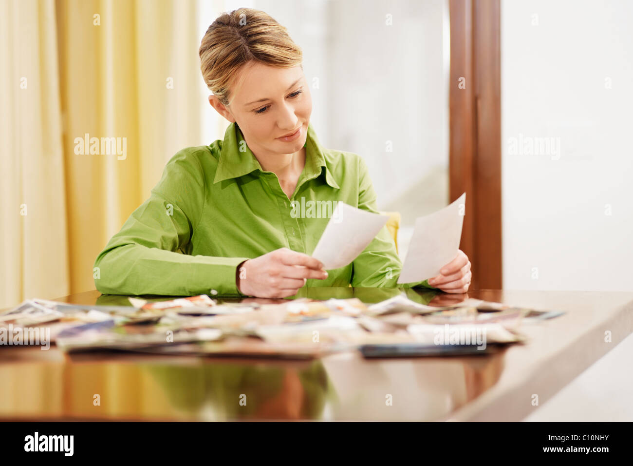 woman sitting and looking at pictures - Stock Image