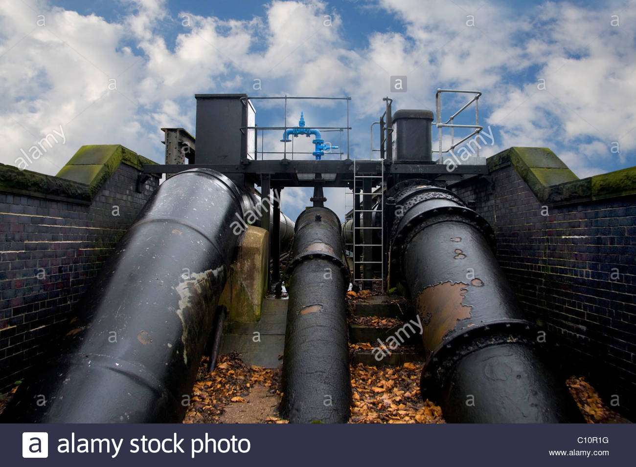 Big pipes and blue tap on a cloudy sky - Stock Image