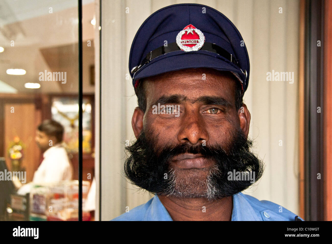 Bellboy with big mustache, bear and hat at the hotel door. - Stock Image