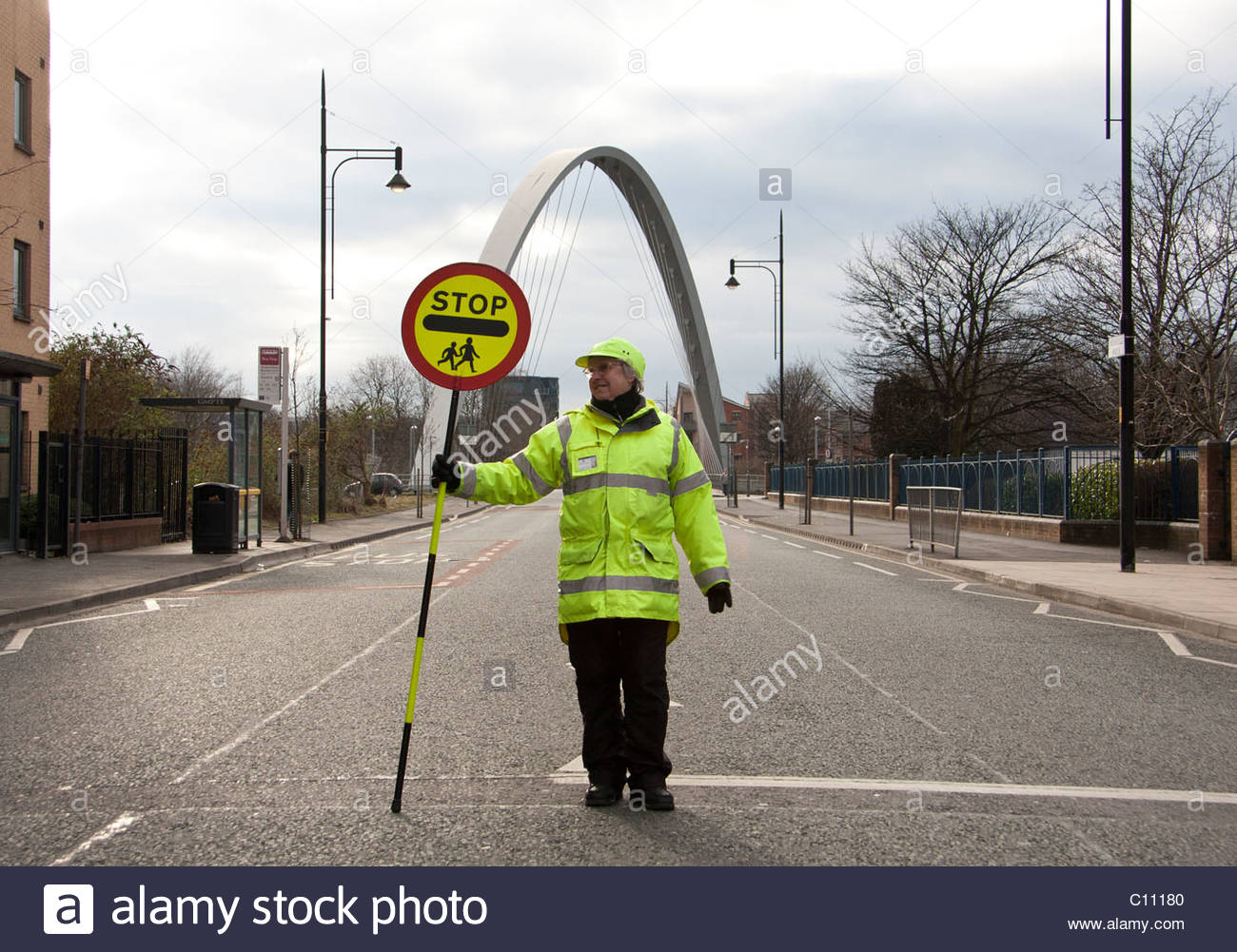 Lollipop lady  in the middle of the street with a stop traffic sign - Stock Image