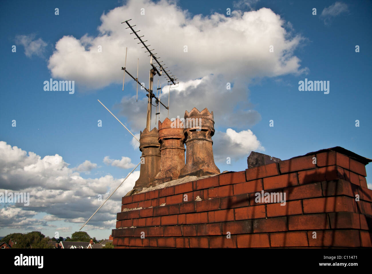English chimneys on red bricks in a blue cloudy sky - Stock Image