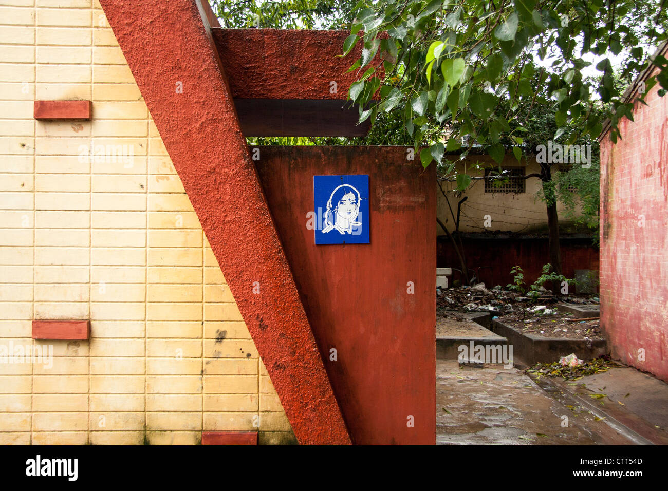 Blue women toilette sign on a red wall surrounded by  trees - Stock Image