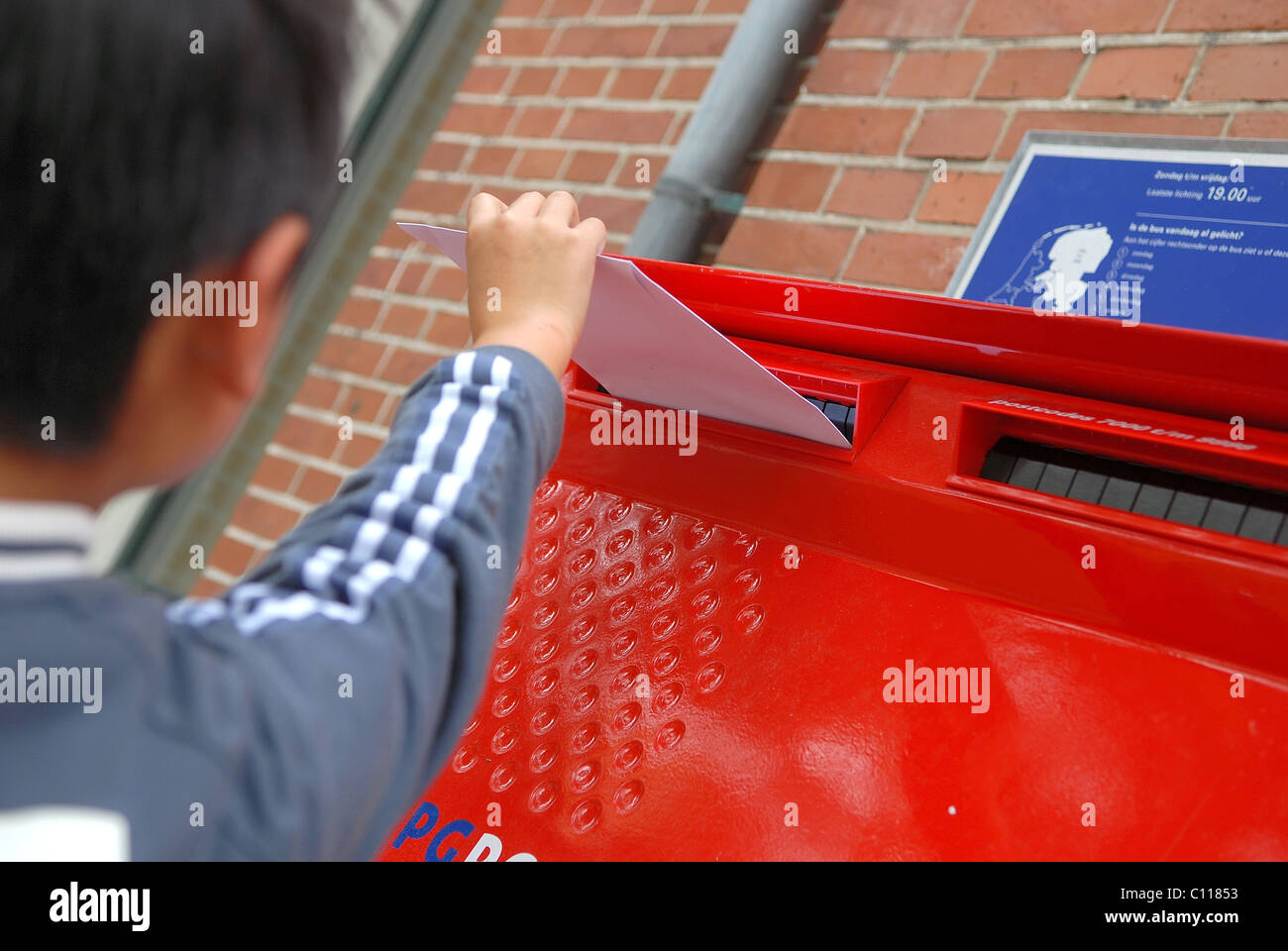 Young boy posting letter - Stock Image