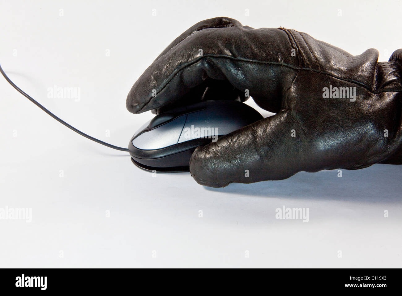 Thief with gloved hand, computer mouse, symbolic image for misuse of data, computer crime - Stock Image