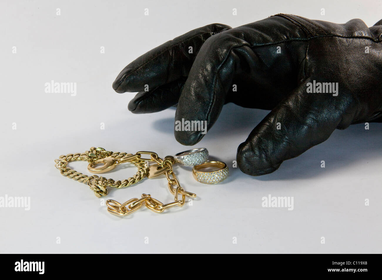 Thief with gloved hand stealing jewelry - Stock Image