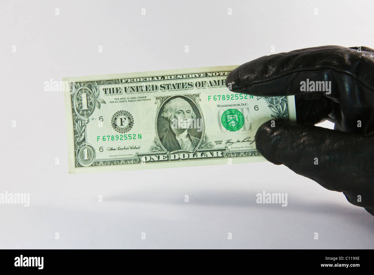 Thief with gloved hand stealing a dollar bill - Stock Image