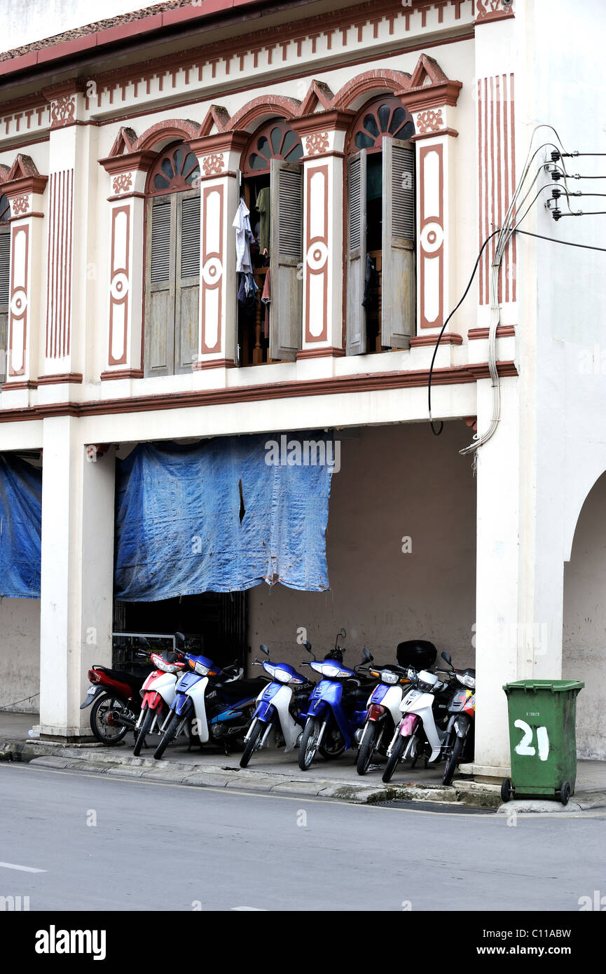 Motorcycles parked under a Chinese shophouse in Kuching, Malaysia - Stock Image