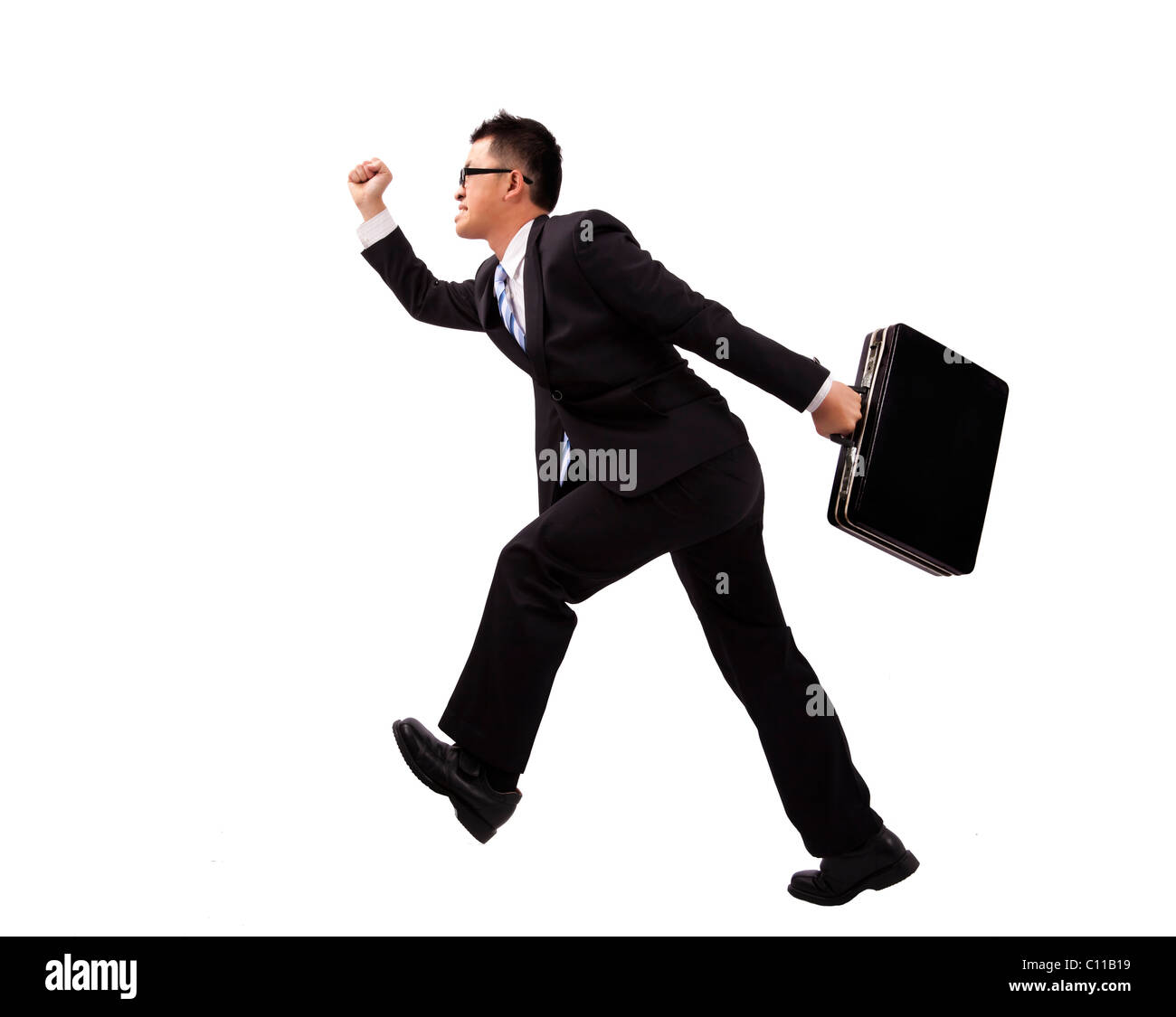 Businessman running with suitcase - Stock Image
