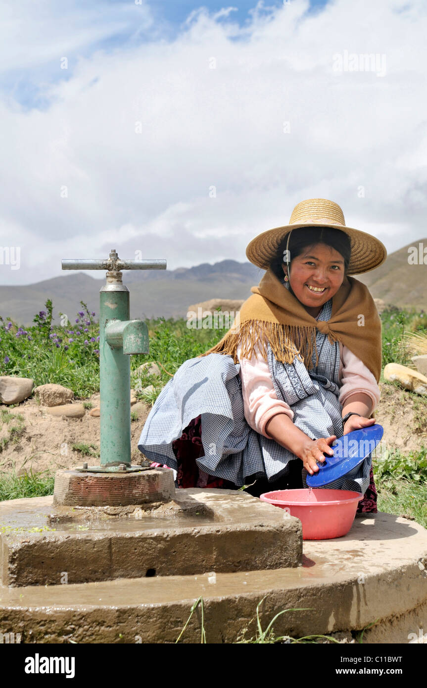 Women in traditional dress of the Quechua doing dishes at the well, Bolivian Altiplano highlands, Departamento Oruro, - Stock Image