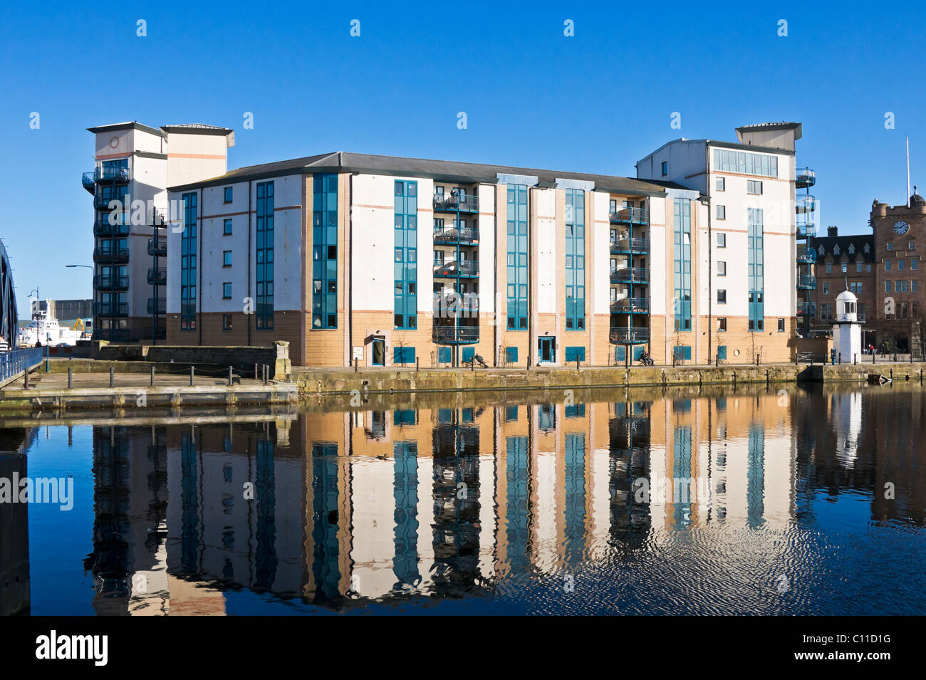 Apartment building and lighthouse (left) on The Shore by Queen's Dock in Leith Docks Edinburgh Scotland - Stock Image
