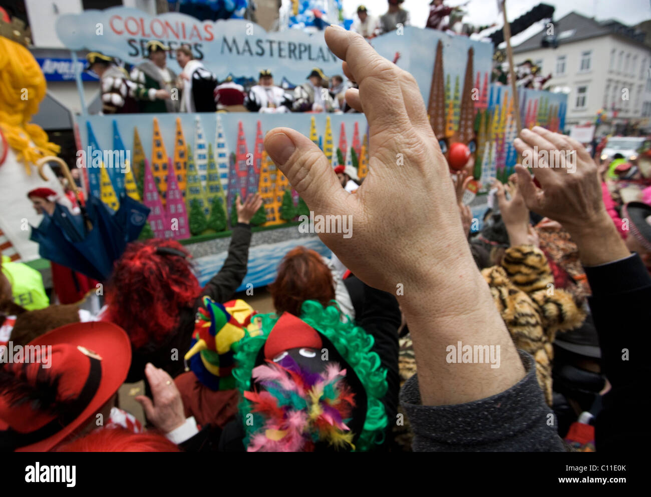 Hands coming out of the crowd to pick up sweets and chocolates thrown at the carnival parade in the streets of Cologne. - Stock Image