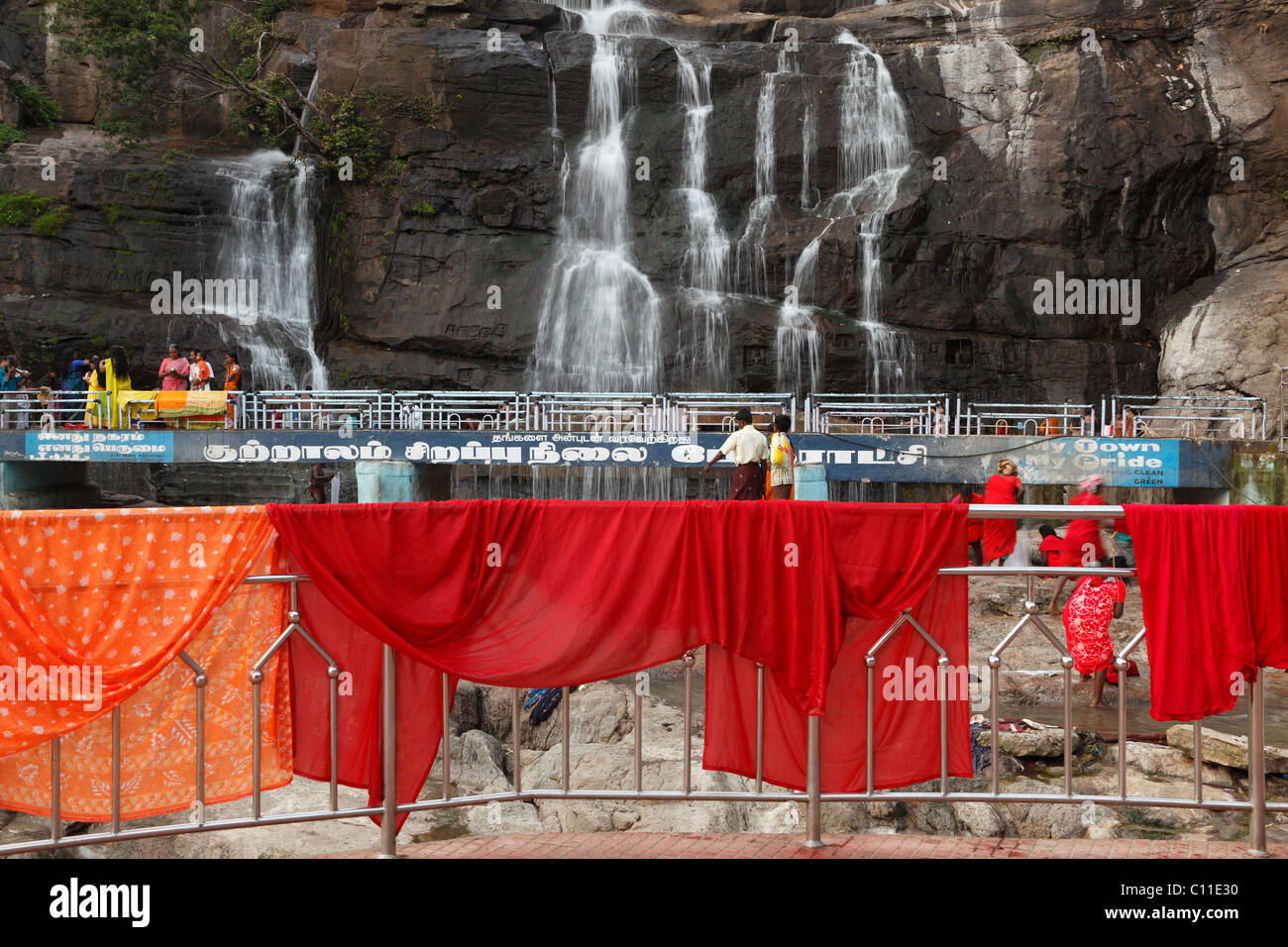 Red cloths hanging out to dry on a railing, Kutralam waterfalls, Peraruvi, Main Falls, Kuttralam, Kuttalam, Courtallam - Stock Image