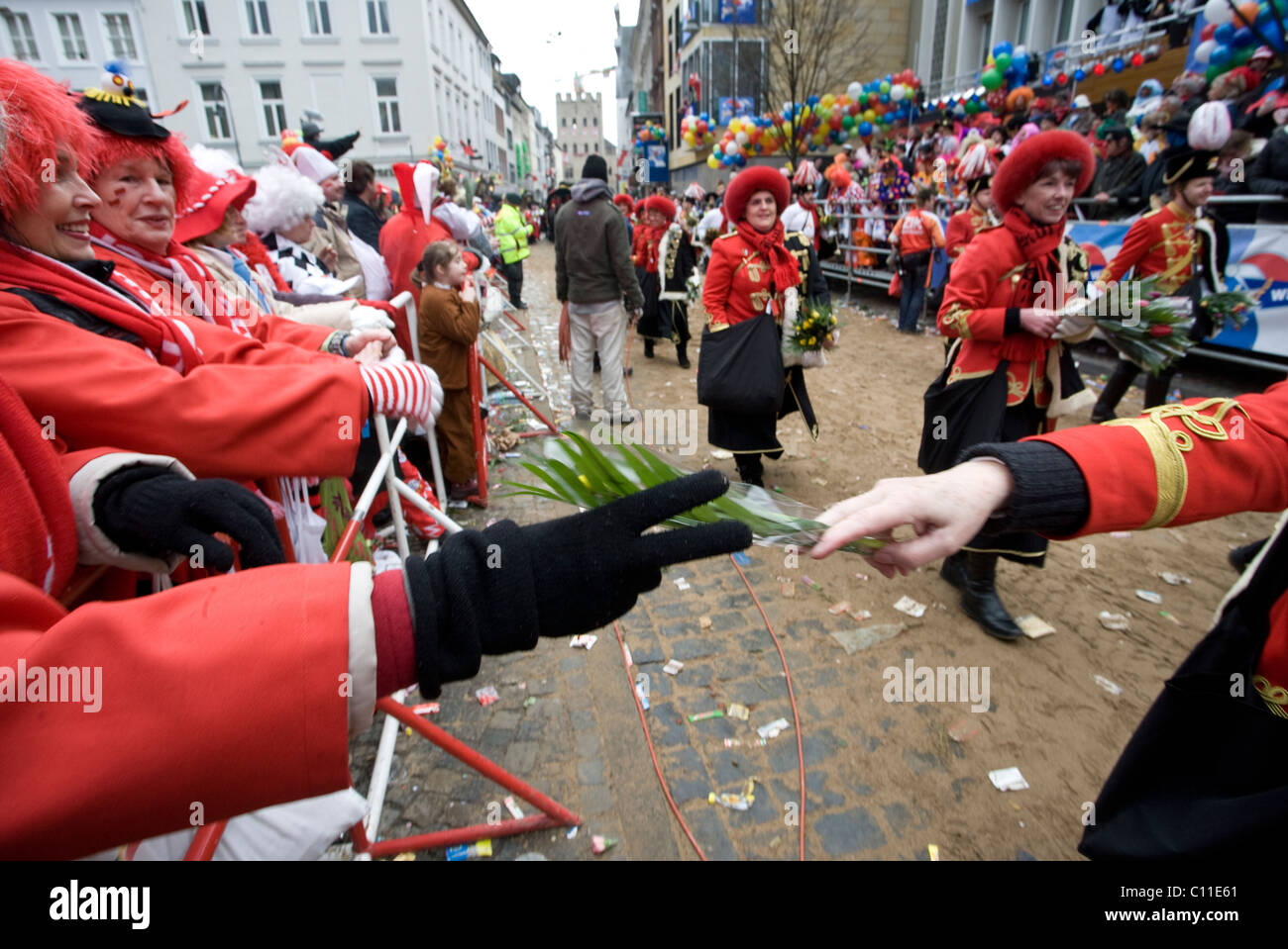 Sweets, chocolates and flowers are given to the crowd during the carnival parade in the streets of Cologne (Germany) - Stock Image
