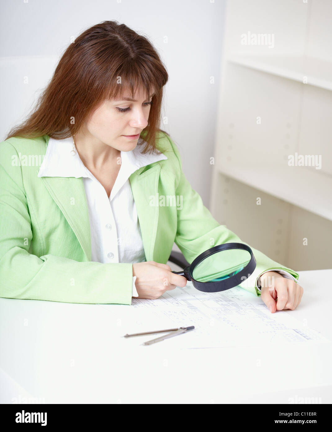 Beautiful girl works with drawing by means of magnifier - Stock Photo
