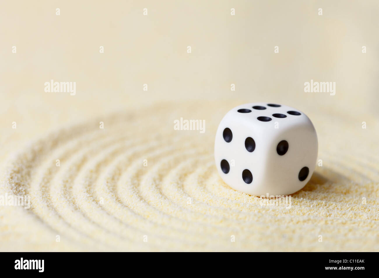 Art composition from playing dice on sand - Stock Image