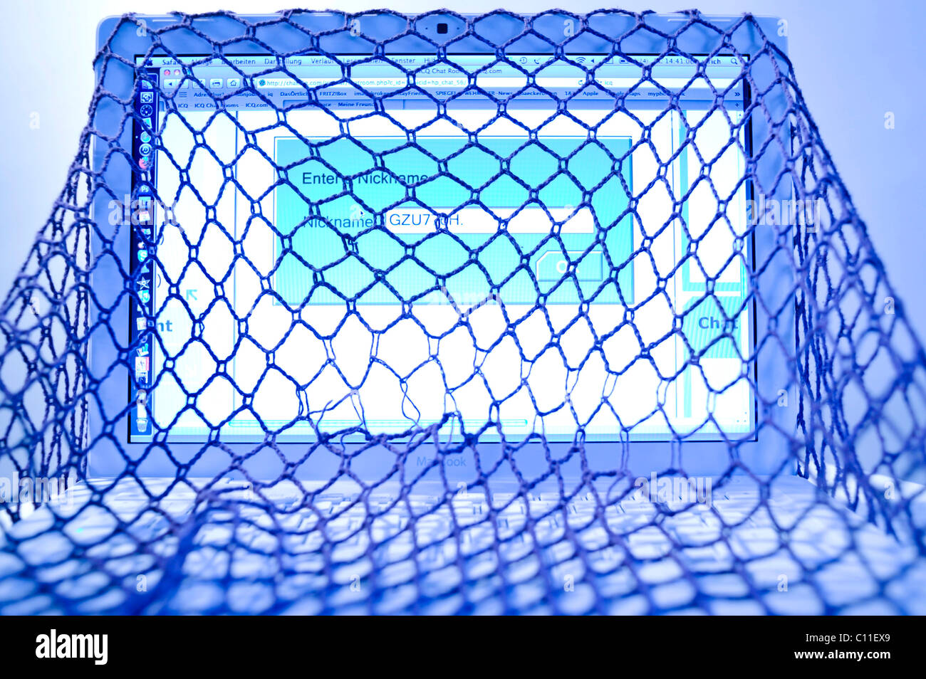 Laptop in a net, symbolic for caught in a net Stock Photo