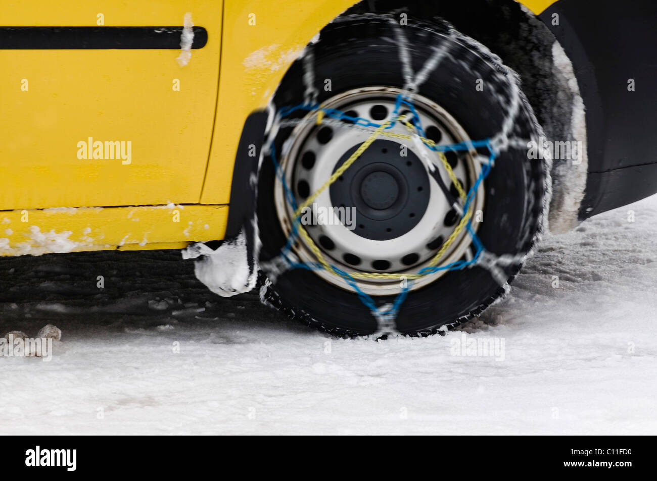 Yellow car driving with snow chains, detail of the rotating front wheel - Stock Image