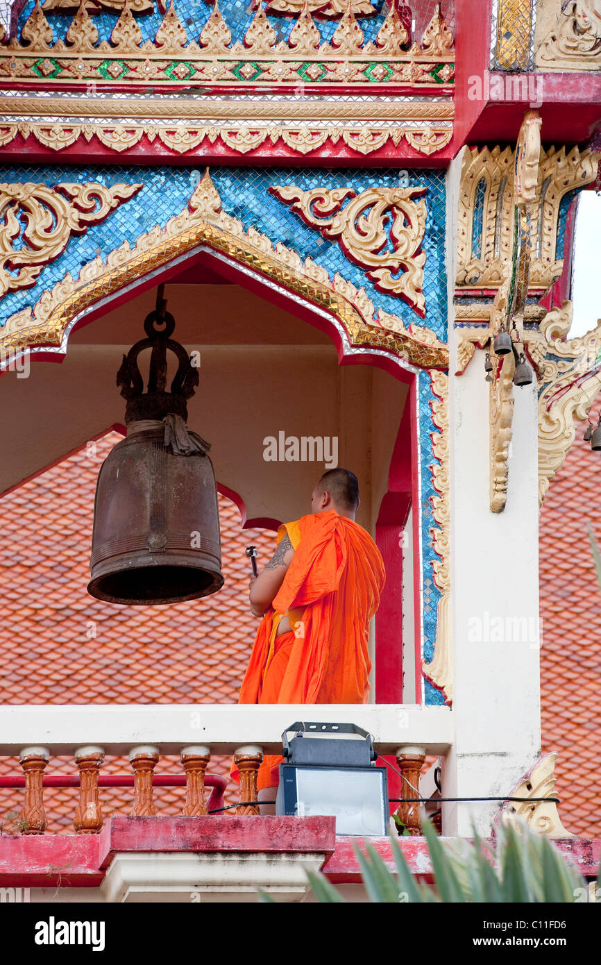A monk ringing for prayers, Wat Chalong, Phuket Island, Southern Thailand, Thailand, Southeast Asia, Asia - Stock Image
