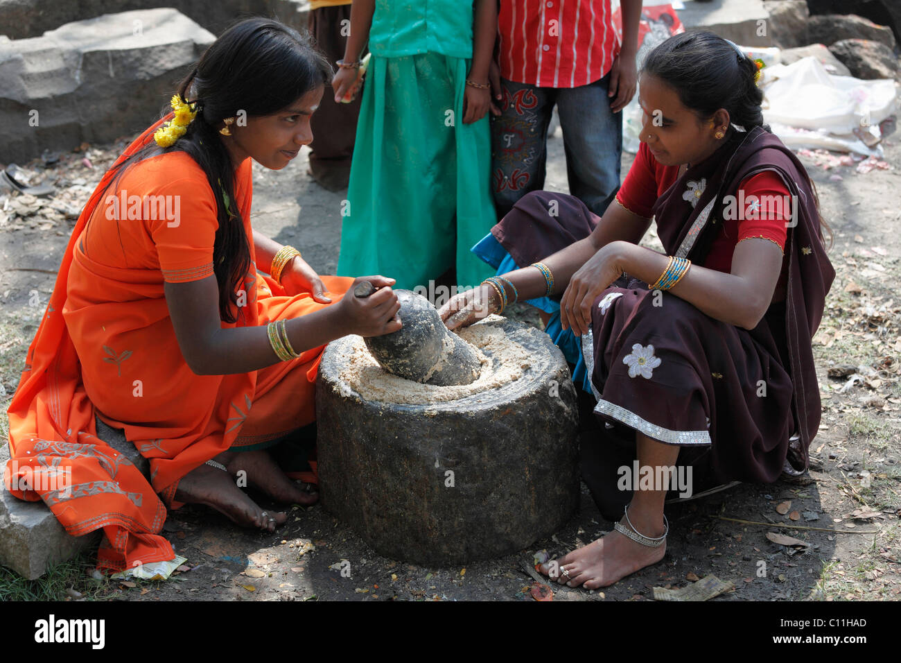 Two girls grindring rice, Nanjangud, Karnataka, South India, India, South Asia, Asia - Stock Image