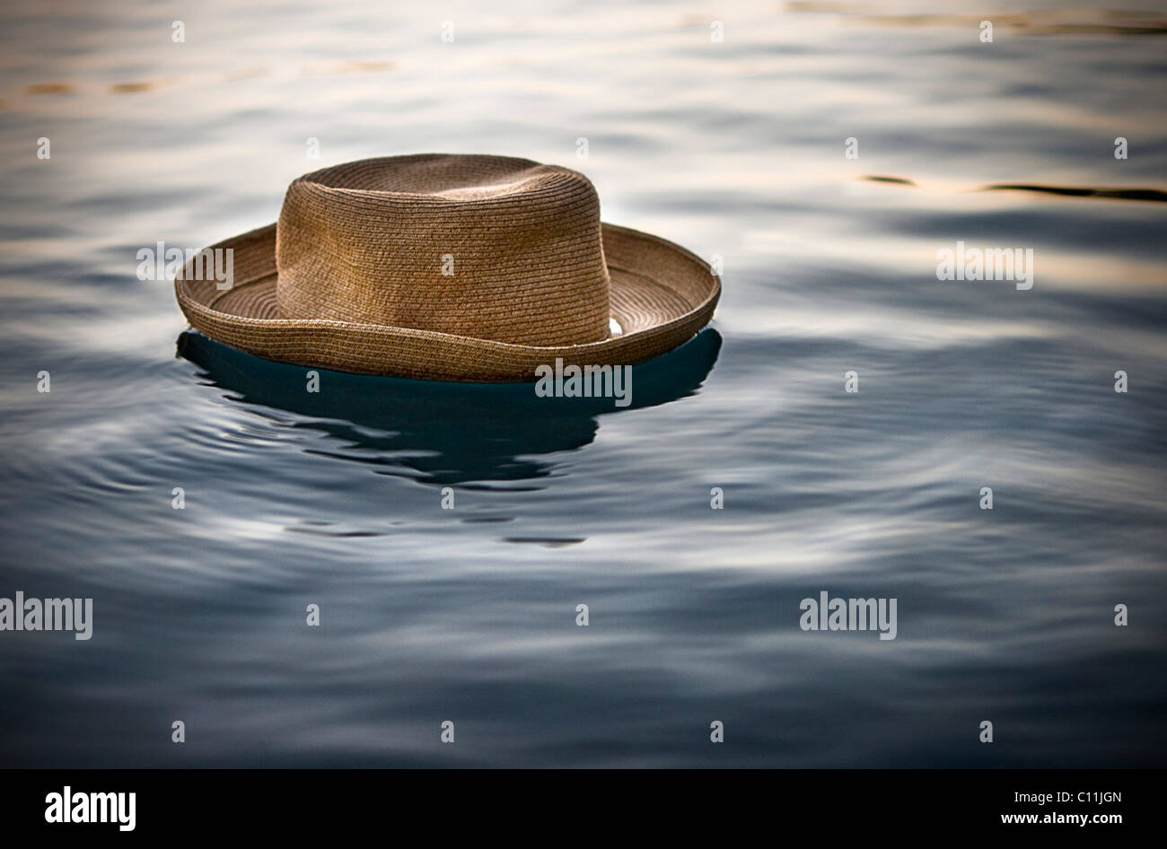 A straw hat floats on the top of a pool of water. - Stock Image
