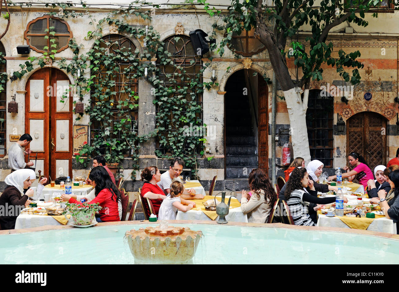 Fountain and guests eating in the courtyard of the Jabri House Restaurant, in an old Muslim palace, historic centre - Stock Image